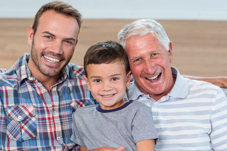senior adult man: Father, son and grandson sitting on sofa and smiling in living room Stock Photo