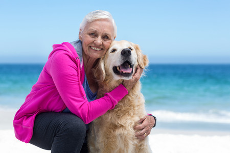 petting: Cute mature woman petting her dog on the beach