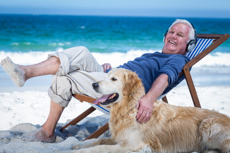 petting: Mature man resting on a deck chair listening to music petting his dog on the beach Stock Photo