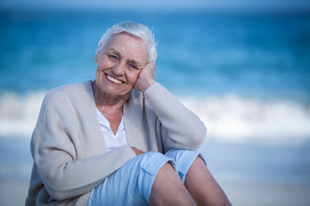 day dreaming: Pretty mature woman day dreaming on the beach Stock Photo