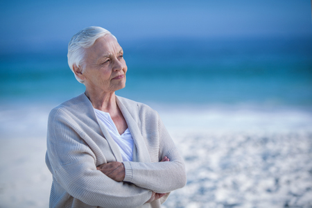 day dreaming: Thoughtful mature woman day dreaming at the beach