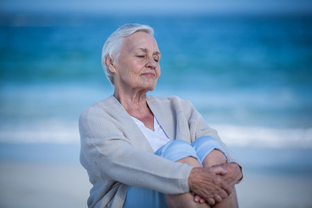 day dreaming: Thoughtful mature woman day dreaming on the beach