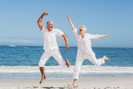 retired couple: Senior couple jumping at the beach on a sunny day