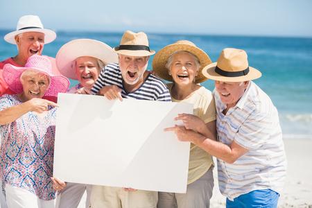 Ältere Freunde, die leeres Papier an einem sonnigen Tag halten