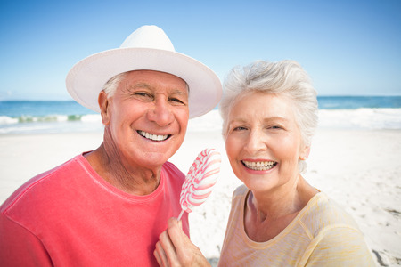 Senior couple eating lollipop on a sunny day Stock Photo - 54391717