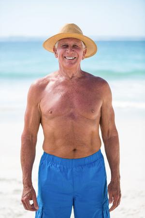 chapeau de paille: Mature man posing with straw hat at the beach Banque d'images