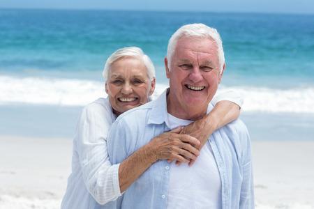 arms around: Senior couple embracing with arms around at the beach Stock Photo