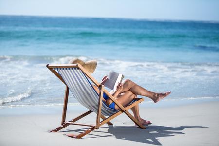 Jolie femme mûre en lisant un livre posé sur une chaise longue sur la plage