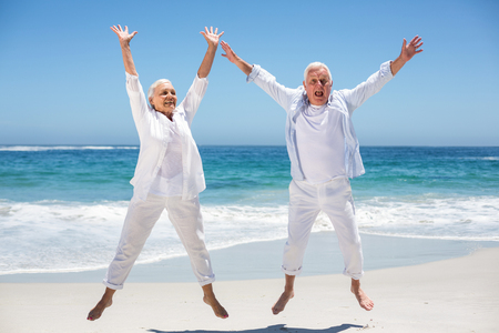Couple de personnes âgées sautant avec les bras levés à la plage
