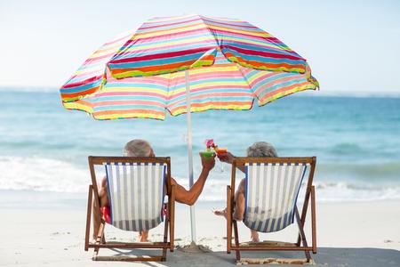 Cute mature couple lying on deckchairs on the beach
