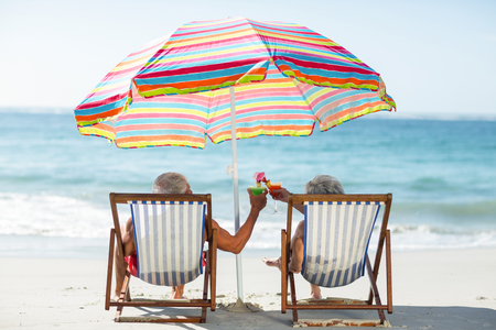 Cute mature couple lying on deckchairs on the beach