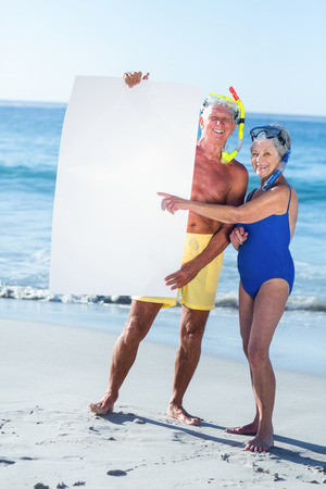 white poster: Senior couple with beach equipment holding a white poster at the beach Stock Photo