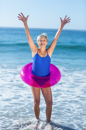 Senior woman with buoy raising arms at the beach Stock Photo