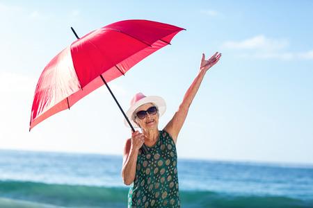 Senior woman posing with an umbrella at the beach