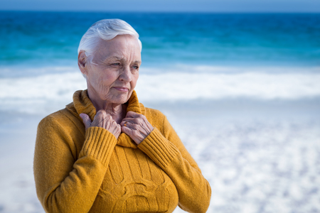 'pull over': Thoughtful senior woman at the beach looking away