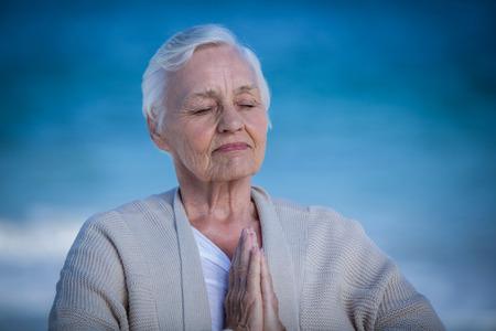 manos unidas: Mujer mayor que se relaja con las manos juntas en la playa