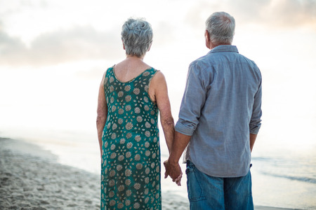 Rear view of a senior couple holding hands at the beach