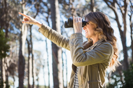 using binoculars: Woman using binoculars in the forest