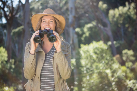 using binoculars: Smiling woman using binoculars in the forest Stock Photo