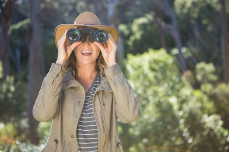 using binoculars: Smiling woman using binoculars in the forest Stock Photo