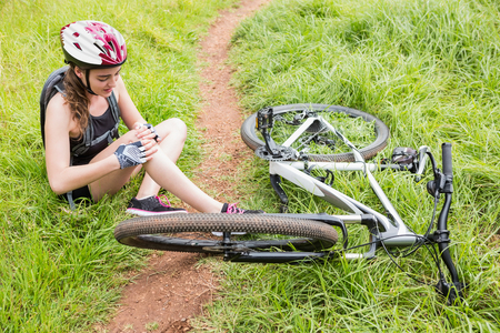 hurting: Woman hurting her leg after having an accident with the bike
