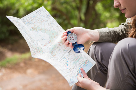 adventuring: Woman checking map and compass in the countryside