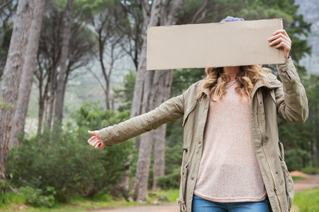 hitch: Hitch hiking woman holding cardboard in the countryside Stock Photo