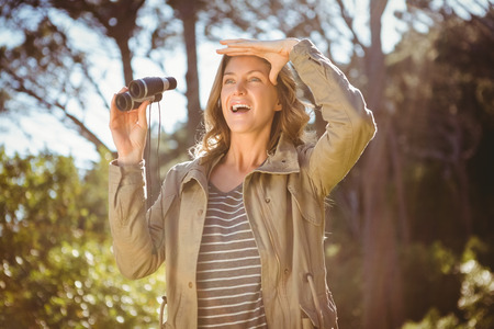 adventuring: Smiling woman holding binoculars in the countryside