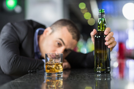 drinks after work: Drunk businessman slumped on bar beside drink