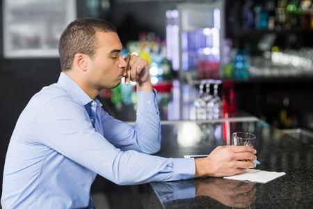 worried businessman: Worried businessman drinking whisky in a bar