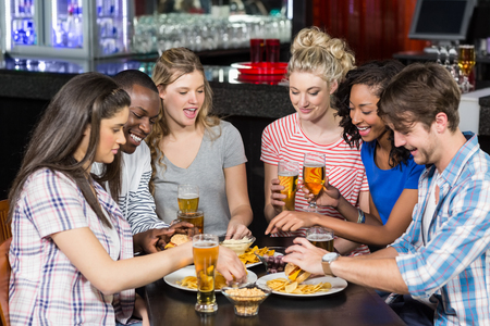 eating fast food: Happy friends having a drink and hamburger in a bar Stock Photo