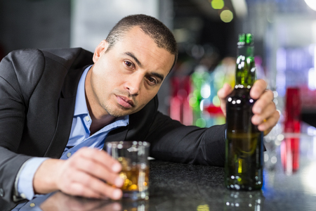 slumped: Drunk businessman slumped on bar beside drink