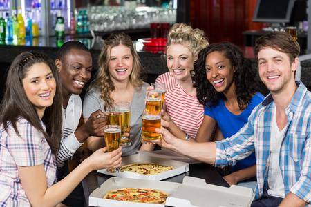 Amici felici che hanno un drink e pizza in un bar