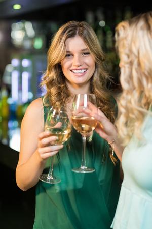 trato amable: amigos felices que tienen una bebida en un bar