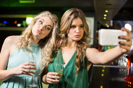 tomando refresco: Smiling friends taking a selfie in a bar