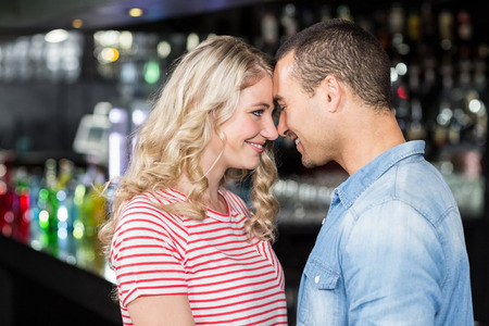 each other: Smiling couple looking at each other in bar
