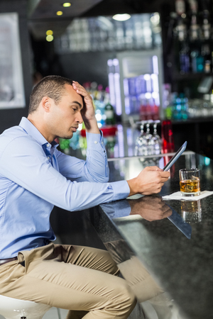 solitariness: Exhausted man having a whiskey in a pub