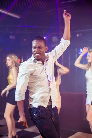 cheerfully: Happy friends dancing cheerfully in night club