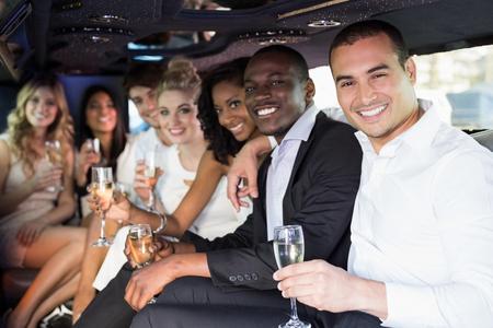 Gut gekleidete Menschen in einer Nacht Champagner in einer Limousine zu trinken aus