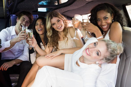 limousine: Happy friends drinking champagne in limousine