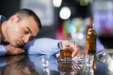 lonesomeness: Tired man having a whiskey and sleeping on a counter in a pub Stock Photo