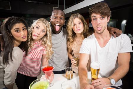 sticking out tongue: Amigos felices con la cerveza y c�cteles sacar la lengua en un bar