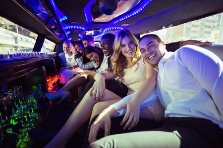 night out: Happy friends chatting in limousine on a night out