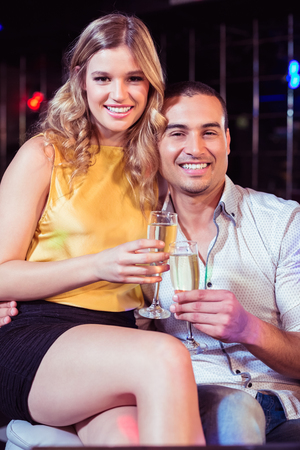 pretty dress: Smiling couple with champagne in a club