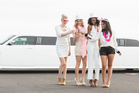 night out: Frivolous women drinking champagne next to a limousine on a night out