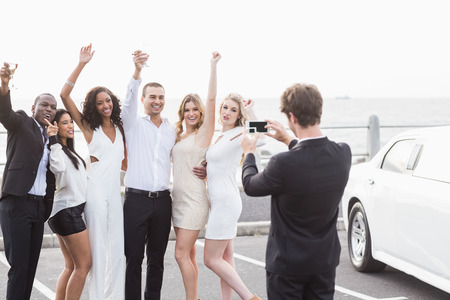together with long tie: Well dressed people taking pictures next to a limousine on a night out