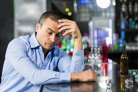 solitariness: Depressed man having a whiskey in a pub