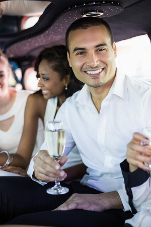 well dressed: Well dressed man drinking champagne in a limousine