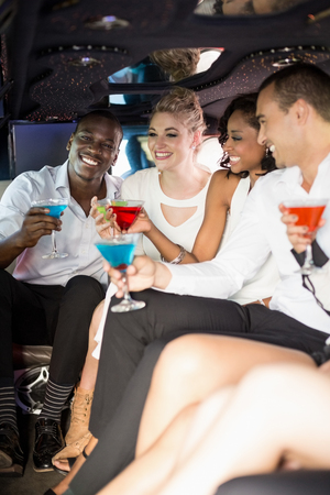 well dressed: Well dressed people drinking cocktails in a limousine on a night out