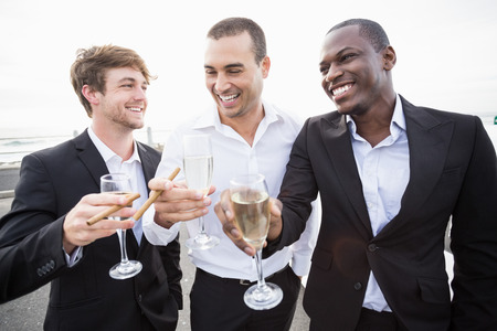 well dressed: Well dressed men drinking champagne next to a limousine on a night out